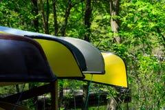 Красочные каноэ или сплавляясь на каяке шлюпки припаркованные в парке курорта embarkation Серия multi покрашенных каяков на банке стоковые изображения