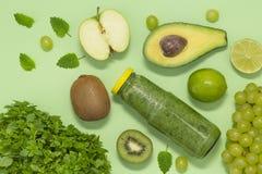 Красочный зеленый smoothie в бутылке на зеленой предпосылке, взгляде сверху стоковые изображения