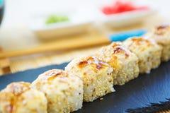 Крены суш установили с семгами, плавленым сыром, красной икрой, авокадоом и wasabi на черном камне на бамбуковой циновке, японско стоковые фотографии rf