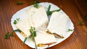 Крен питы с листьями, зелеными цветами и сосиской салата в плите сток-видео