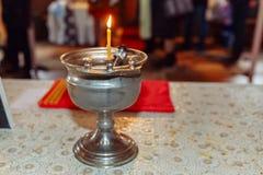 Крестить шрифт с освещенной свечой стоковое фото
