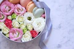 Круглая коробка с цветками и печеньями миндалины на мраморной предпосылке стоковое изображение