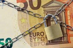 Крупный план банкноты евро, который 50 заперли с цепью и padlock - концепцией страхования, порук-в и финансовой обеспеченности стоковые изображения
