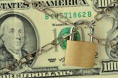 Крупный план банкноты доллара, который заперли с цепью и padlock - концепцией страхования, порук-в и финансовой обеспеченности стоковая фотография