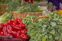 Крупный план богатых красных болгарских перцев с правдивостью зеленого овоща показанной на зеленом рынке стоковое фото
