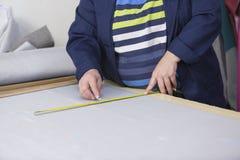 Крупный план более старой женщины в фабрике мебели которая измеряющ и отмечать серый материал для софы с чуркой стоковое фото