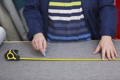 Крупный план более старой женщины в фабрике мебели которая измеряющ и отмечать серый материал для софы с чуркой стоковые изображения rf