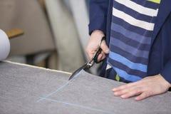 Крупный план более старой женщины в фабрике мебели которая режет серый материал для софы стоковое изображение rf