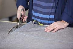 Крупный план более старой женщины в фабрике мебели которая режет серый материал для софы стоковые фото