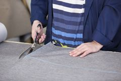 Крупный план более старой женщины в фабрике мебели которая режет серый материал для софы стоковое фото rf