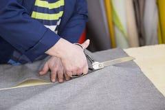 Крупный план более старой женщины в фабрике мебели которая режет серый материал для софы стоковое фото