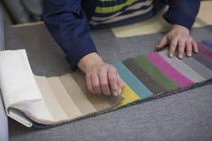 Крупный план более старой женщины в фабрике мебели которая комплектует материал для софы стоковые изображения rf