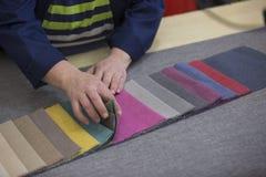 Крупный план более старой женщины в фабрике мебели которая комплектует материал для софы стоковые изображения