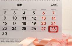 Крупный план календаря с красным знаком на дне, ленте и пер пасхи Концепция торжества пасхи врага подготовки стоковые изображения rf