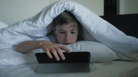 Крупный план мальчика наблюдает мультфильмы на цифровом планшете вечером под одеялом Концепция электронной наркомании видеоматериал