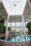 Крытый бассейн с белыми столбцами и листвой стоковые фотографии rf