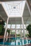 Крытый бассейн с белыми столбцами и листвой стоковая фотография