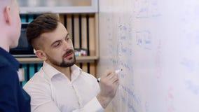 Коллеги людей в офисе работают на проекте, делают примечания на белой доске с отметкой сток-видео