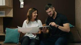 Коллеги человек и женщина обсудить совместный проект используя чертеж и планшет сидя на кресле в офисе видеоматериал