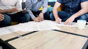 Коллеги работают с чертежи в офисе таблицей, правильные неточности с планшетом Руки на таблице сток-видео