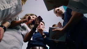 Коллеги обсуждают проблему используя мобильные телефоны и планшеты устройств, стоя в круге Нижний взгляд сток-видео