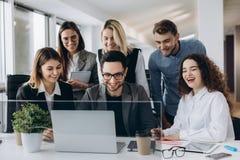 Команда дела запуска на встрече в современном ярком интерьере офиса усмехаясь и работая на ноутбуке стоковая фотография