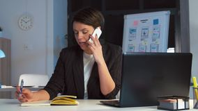 Коммерсантка вызывая на смартфоне на темном офисе видеоматериал