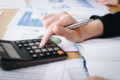 Коммерсантка работая на калькуляторе для того чтобы высчитать коммерческие информации финансовый отчет на таблице стоковое фото