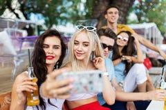 Компания симпатичных друзей смеясь и выпивая желтыми коктейлями, общаясь и делая selfie на таблице внутри стоковое изображение