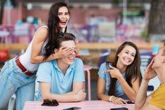 Компания симпатичных друзей смеющся и сидящ на таблице в славном кафе лета Развлечения, имеющ стоковое фото rf