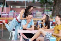 Компания симпатичных друзей смеющся и сидящ на таблице в славном кафе лета Развлечения, имеющ стоковые изображения