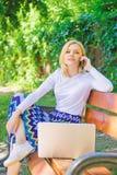 Компьтер-книжка женщины в парке наслаждается зеленой природой и свежим воздухом Девушка мечтательная пользуется онлайн покупками  стоковое фото