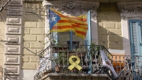 Конец-вверх Балкон на доме в Барселоне куда помещены флаг Каталонии и желтая лента протеста _ сток-видео