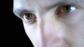 Конец-вверх глаз и смотреть на молодого человека работая на компьютере на черной предпосылке сток-видео