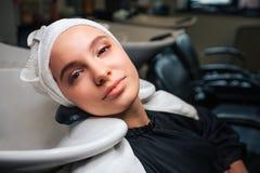 Конец-вверх красивой расслабленной женщины с полотенцем на голове смотря камеру после профессиональной стирки волос Уход за волос стоковые изображения