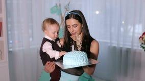 Конец-вверх небольшого годовалого мальчика есть торт с его руками и кормить его мать сток-видео