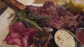 Конец вверх по зажаренному мясу с косточкой нервюры лежа на пите с красной капустой, мозоль, грибы, морковь и соусы закрывают вве видеоматериал