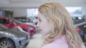 Конец вверх по милой белокурой женщине идя между строками новых автомобилей в мотор-шоу смотря вокруг выбора одного купить Концеп видеоматериал
