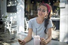 Конец вверх по привлекательной молодой модели в головном платке и круглых солнечных очках представляет на открытом воздухе стоковое фото rf