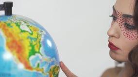 Конец вверх по девушке портрета молодой красивой курчавой с ярким составляет изучать глобус выбирая страну акции видеоматериалы
