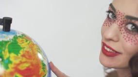 Конец вверх по девушке портрета молодой красивой курчавой smilling с ярким составляет изучать глобус выбирая страну сток-видео