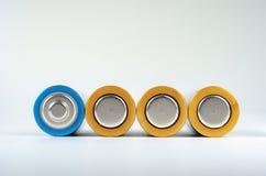 Конец-вверх 4 сине-золотой батарей AA на белой предпосылке Малая глубина поля, макроса стоковая фотография