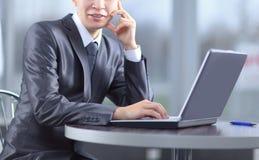 конец вверх усмехаясь бизнесмен сидя перед открытым ноутбуком стоковое изображение rf