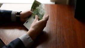 Конец-вверх рук бизнесмена считая 100 счетов евро на таблице акции видеоматериалы