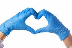 Конец-вверх рук в перчатках латекса Сердце сложено от рук Валентайн формы влюбленности сердца карточки стоковое фото
