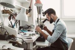 конец очень Взгляд со стороны мужского ювелира смотря новый продукт украшений через микроскоп в мастерской стоковые фото