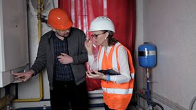 Контролер и работник проверяют систему отопления Красивый инженер женщины сток-видео