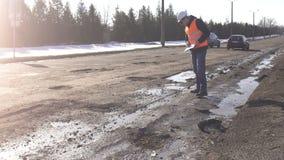 Контролер рассматривает и проверяет отверстия в дороге, плохую дорогу видеоматериал