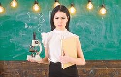Концепция биологии Дама в официально носке на спокойной стороне в классе Ученый дамы держит книгу и микроскоп, доску дальше стоковое фото