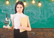 Концепция биологии Учитель биологии держит книгу и микроскоп Дама в официально носке на спокойной стороне в классе Дама стоковое изображение
